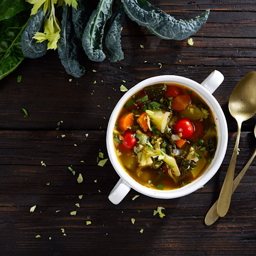 A vegetable soup on a wooden table and 2 spoons on the side.