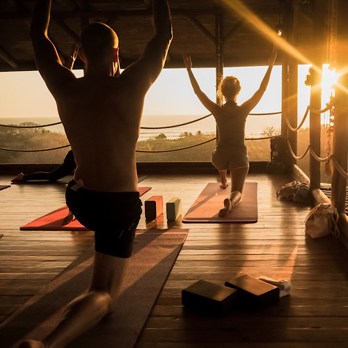 A man and a woman doing yoga facing the sunrise.