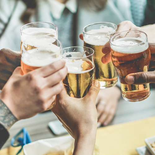 Group of people raising their glass of beer for a toast.