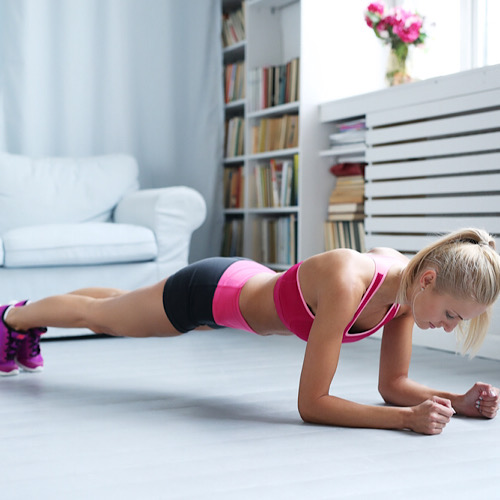A woman doing planks at home.