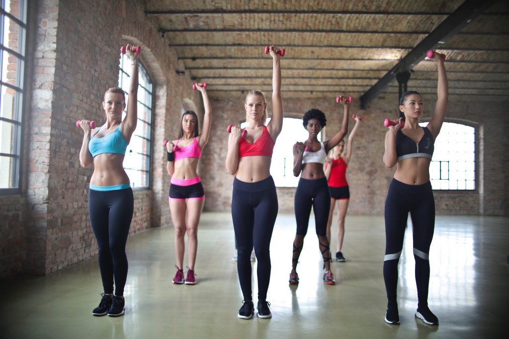 A group of inter racial women doing a strength training that benefits women.