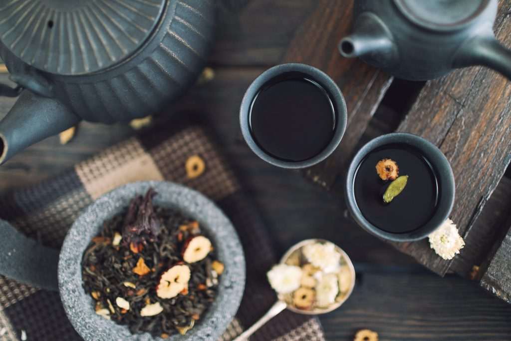 Top view image of two cups of tea and two pots with some seeds on the side.
