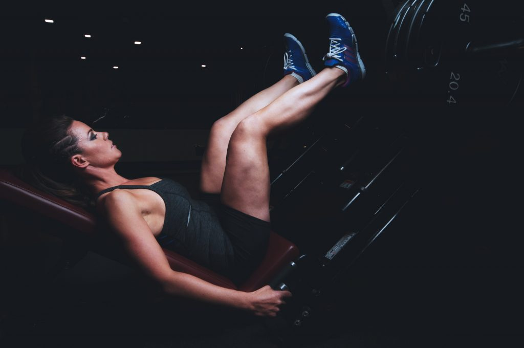 A fit woman on a leg press doing her booty building workout.