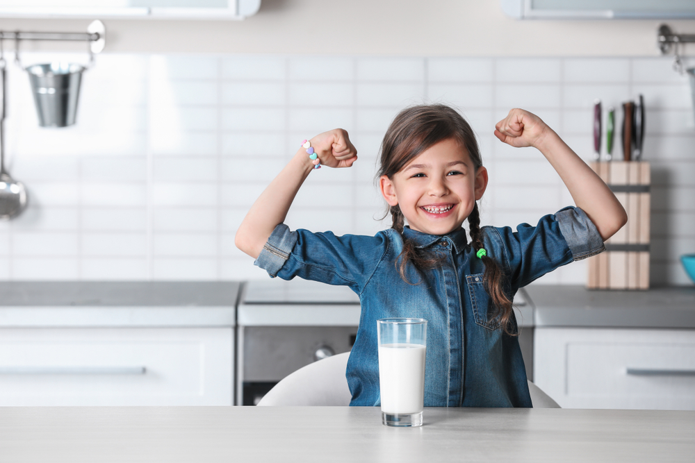 Little girl flexing muscles on both arms after drinking milk, as a sign that she's stronger.