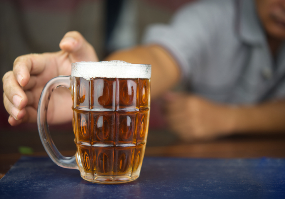 Man reaching for a mug of beer. With moderation and the right selection, drinking beer and dieting can be done at the same time.