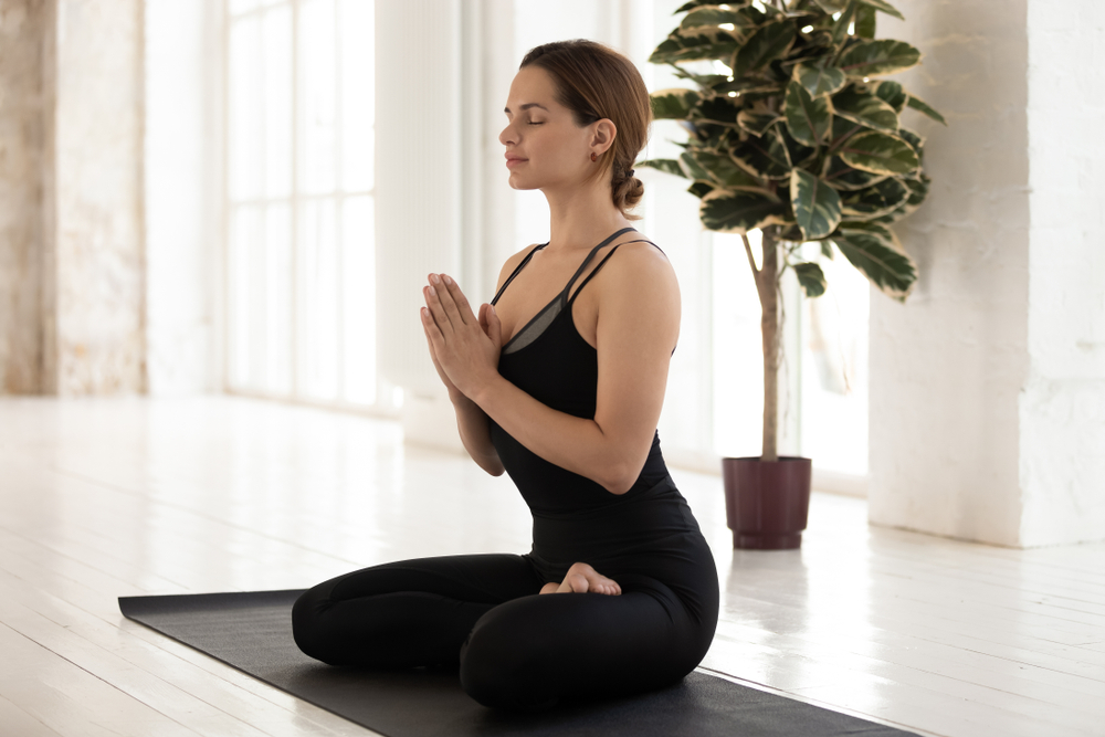 Woman doing mindfulness retreats by meditating on a yoga mat.