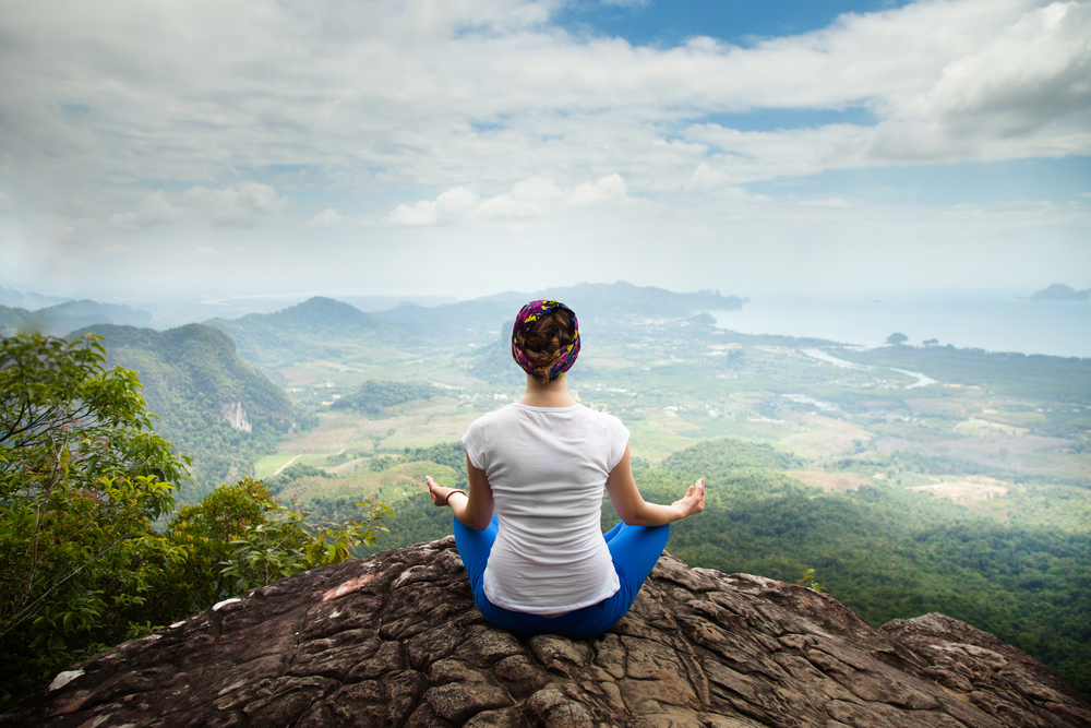 Woman at a mindfulness retreat, meditating on a mountaintop.