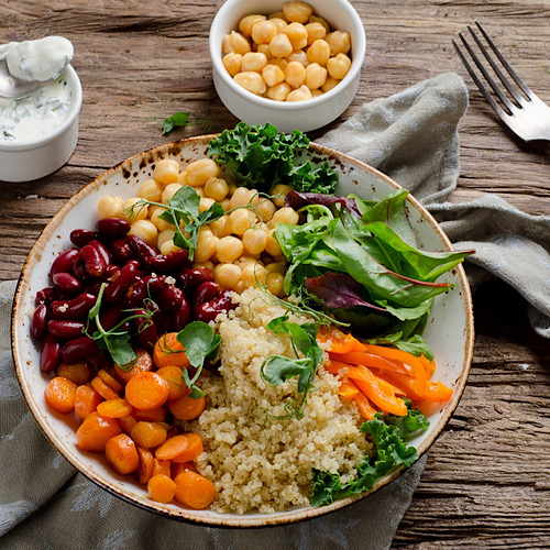 A vegetarial meal with cauliflower rice, carrots, red beans, and some leaves and a small bowl of dip and a fork on top of a wooden table.