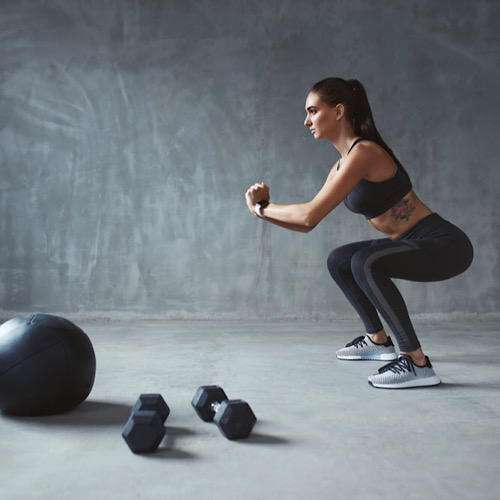 A fit woman doing squats and 2 dumbbells on the floor and a medicine ball.