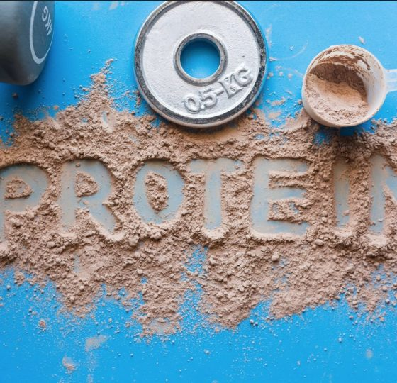 Protein powder scattered on a surface forming the word protein.