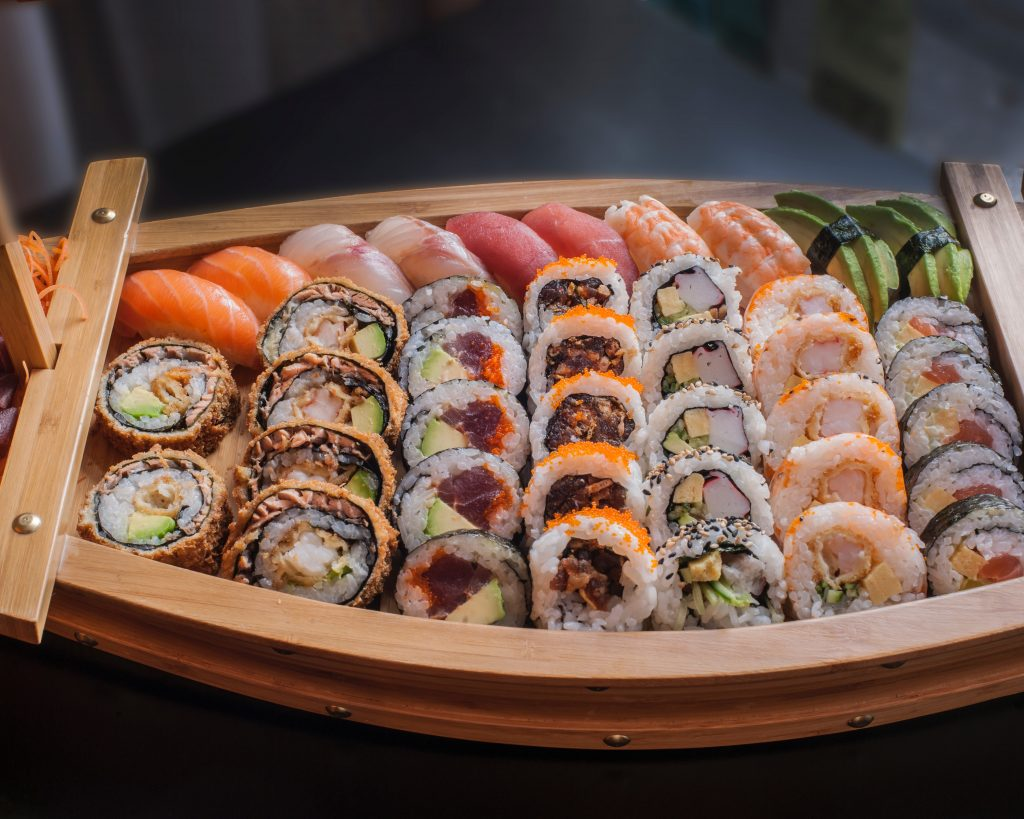 Assortment of sushi in a wooden boat platter. Looks amazing but is sushi healthy for you?