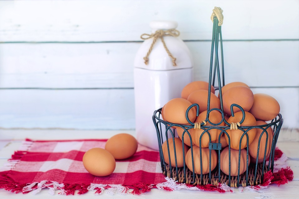 Brown eggs in a basket next to a jar of milk a good mood boosting food.
