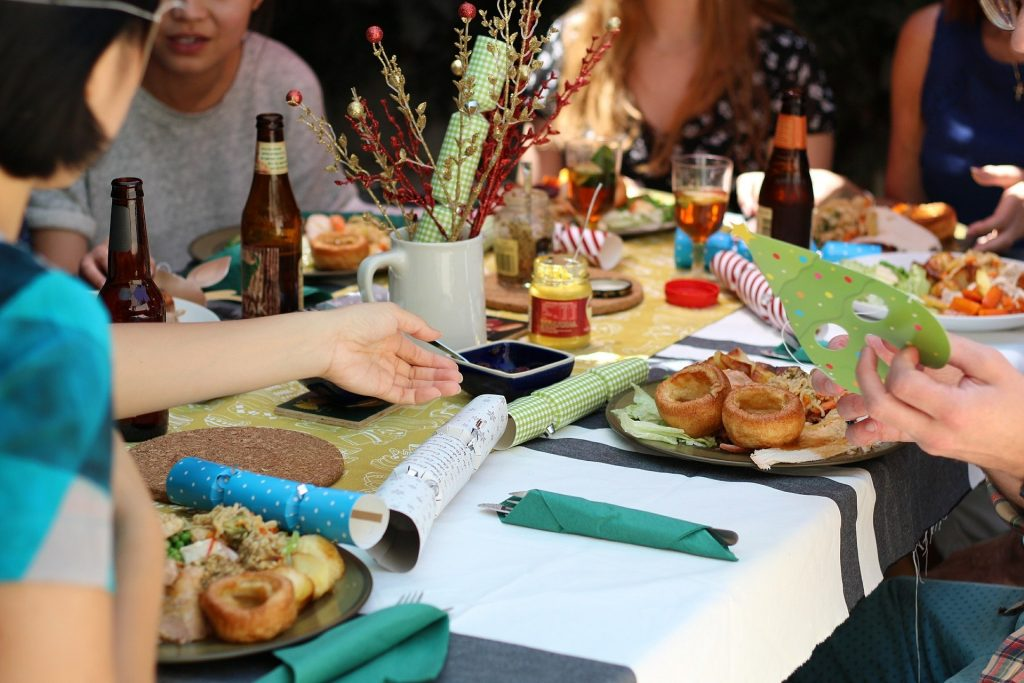 Friends eating dinner at the table can avoid holiday weight gain too.