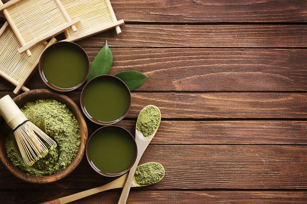 Green tea in cups on a wooden table.