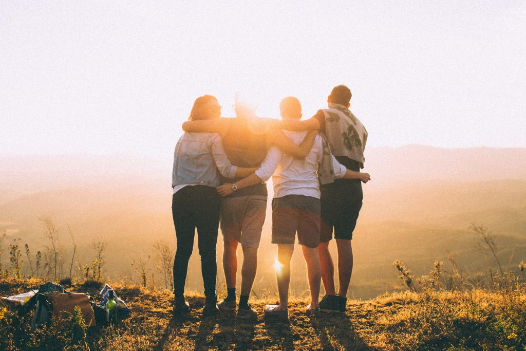Group holding each other facing the sun.