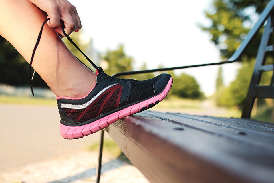 A person stopping to tie their laces while running. Would laceless sneakers save them time?