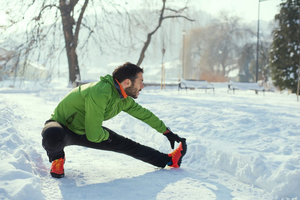 Man stretching in the snow. This is a good preparation for cold weather running.