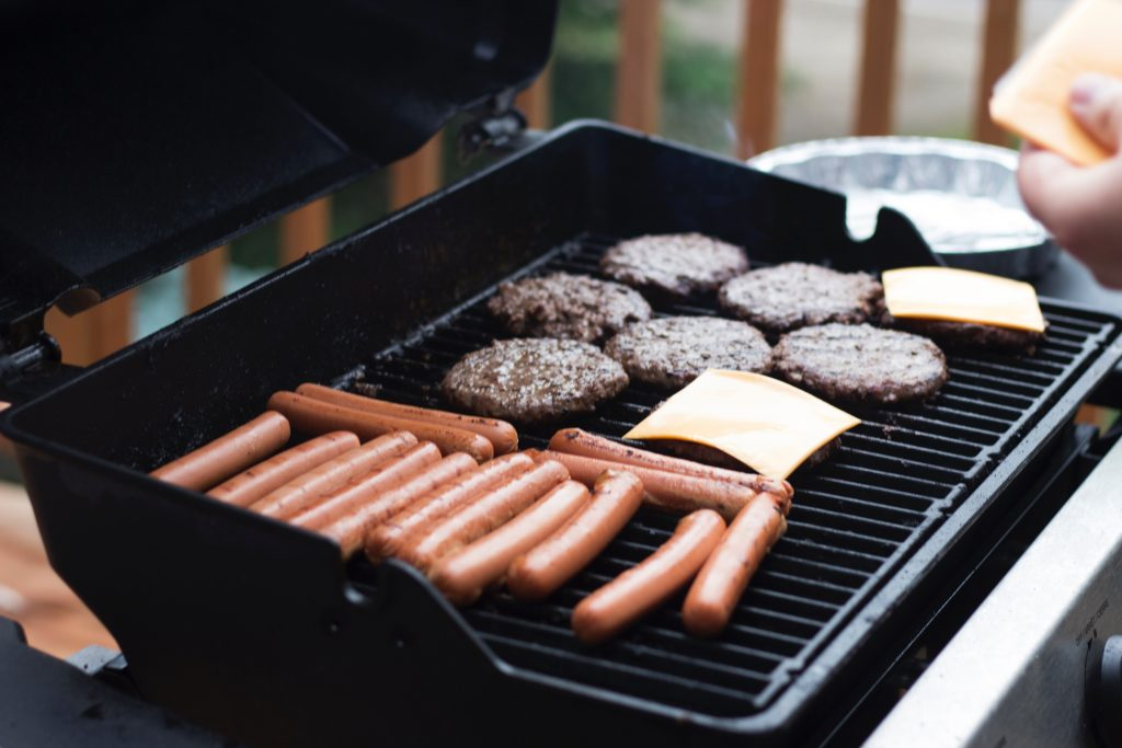 Burgers and hot dogs cooking on a grill. Would you like some healthy ground beef recipes?