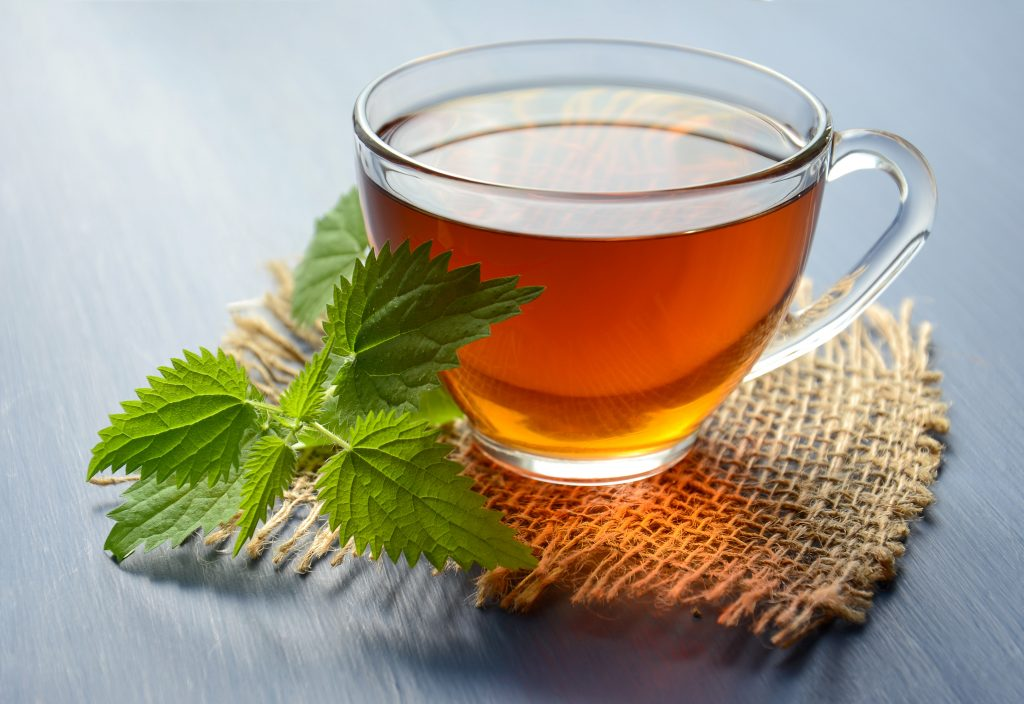 a close up photo of peppermint tea in a cup next to peppermint leaves