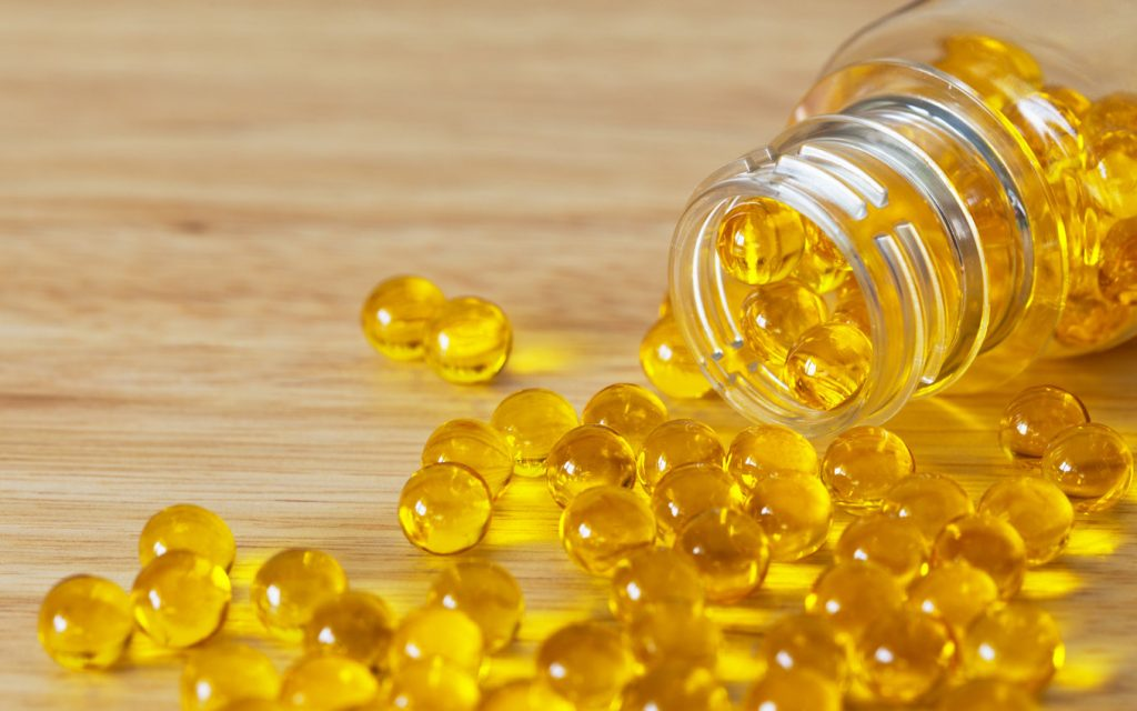 Which vitamins are fat soluble? Softgel capsules with fat-soluble vitamins scattered on a wooden surface is an example.