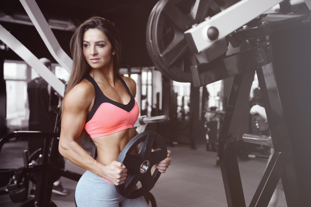Fit Woman holding weight plate.