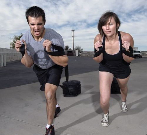 A man and woman doing sled training