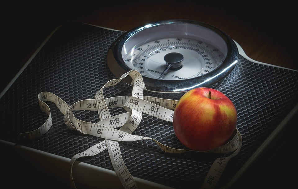 An apple and a tape measure on the top of a bathroom scale to illustrate weight loss strategies