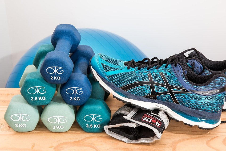 Stack of dumbbell and a pair of sneaker. Should you do cardio before or after weights?