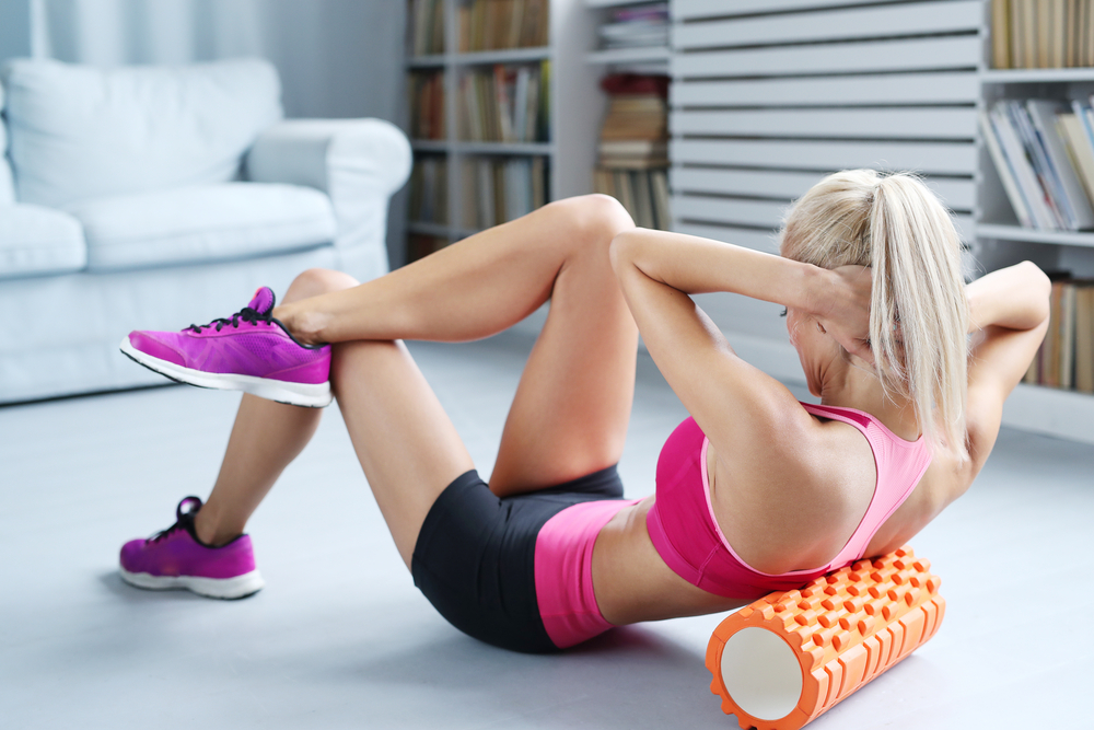 A woman using foam roller on her back to cover a larger area of muscles.