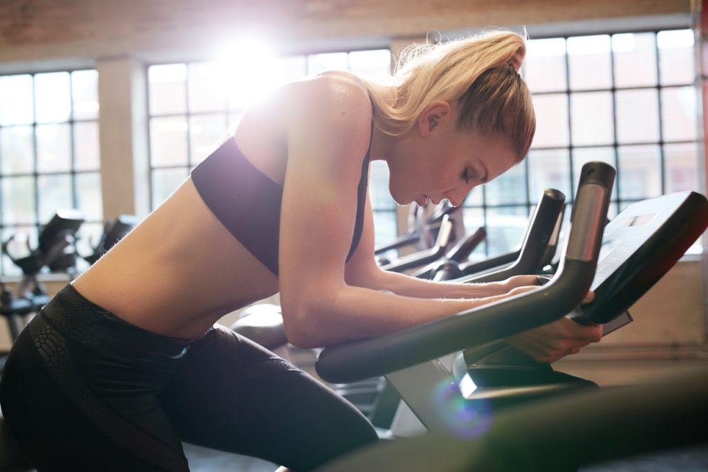 Woman taking a break during a stationary bicycle workout.
