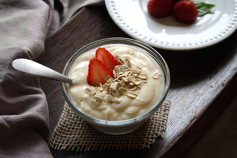 Yogurt in a bowl with strawberry and outs on top on a wooden table.