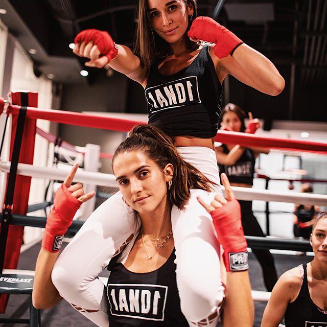 Amanda Carola and Amanda Riley striking poses next to a boxing ring.