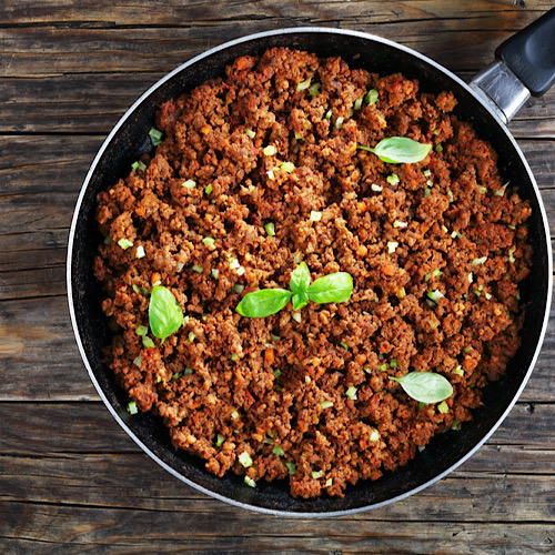 Ground beef stewed in tomato sauce in a pan.