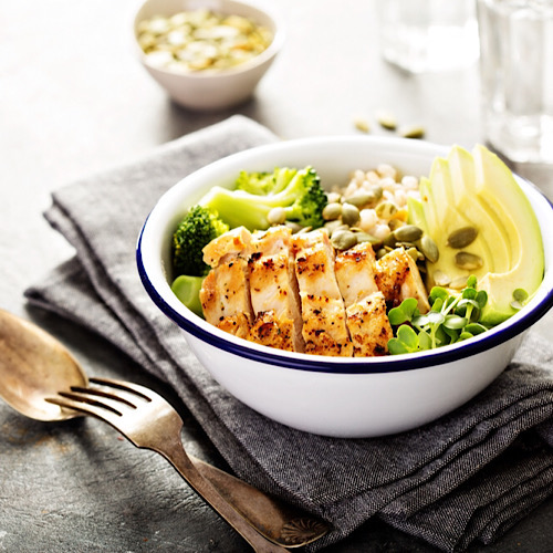 A bowl of grains with chicken, broccoli and slices of avocados on top of a napkin and a spoon and fork on the side.