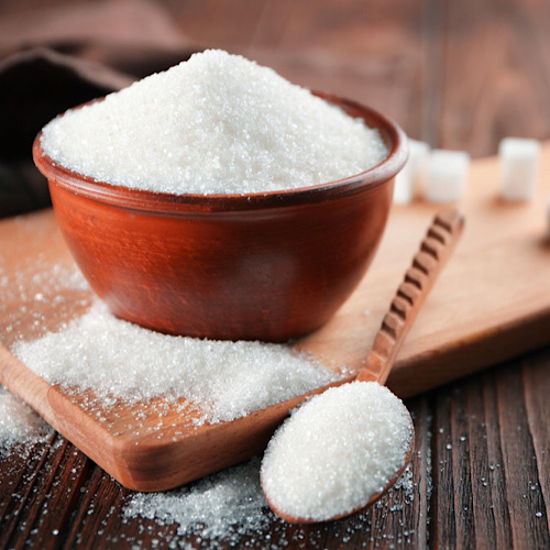 A bowl full of sugar on top of a wooden board with spilled sugar and a spoonful of sugar.