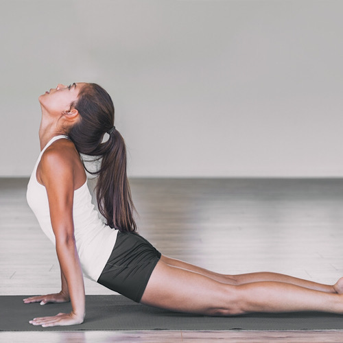 Fit woman doing stretching on a yoga mat.