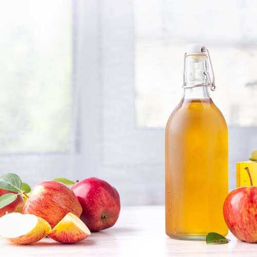 Apples and a bottle of apple cider vinegar on table top.