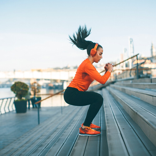 A woman doing Jump squats on a concrete stairs outdoors.