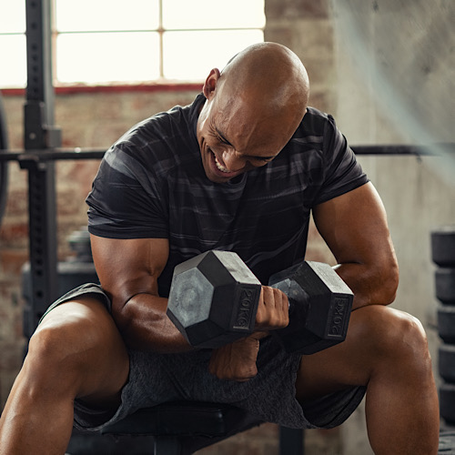 A man lifting a dumbbell for bicep workout.