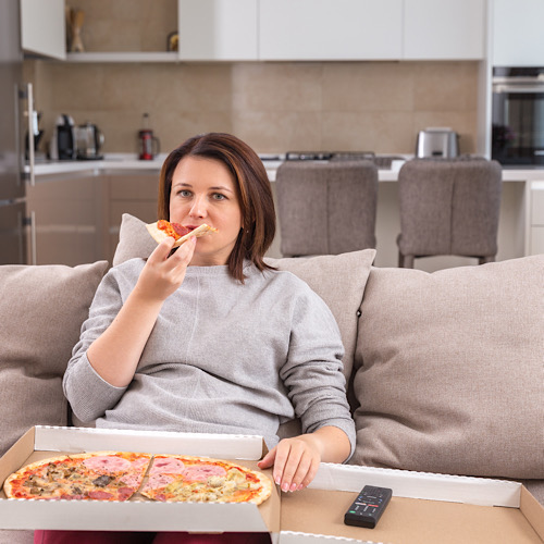 Woman eating pizza on a couch.