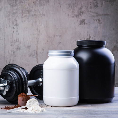 Two protein powder containers next to a dumbbell
