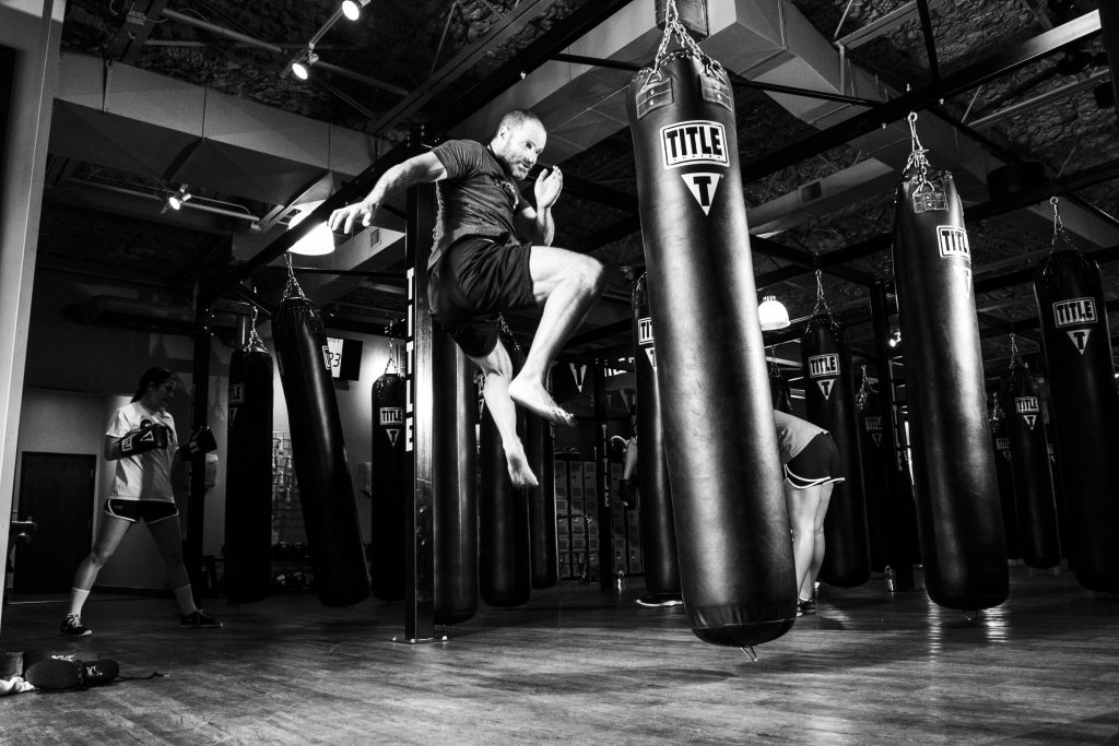Man kicking heavy bag.