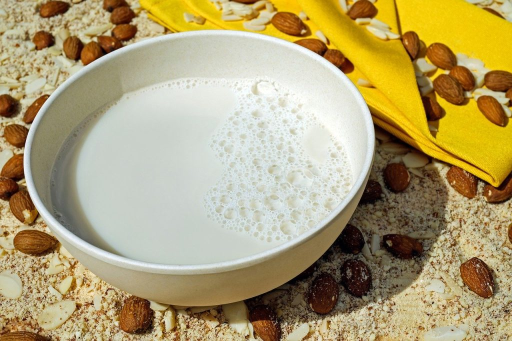 A bowl of almond milk surrounded by scattered almonds.
