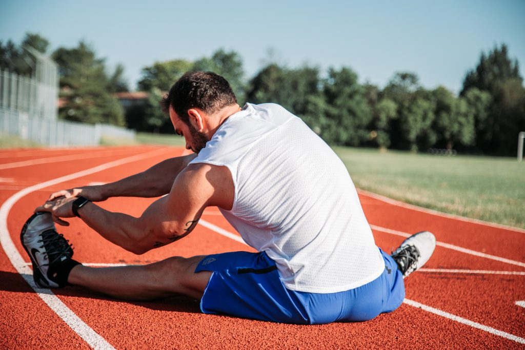 Man doing some stretches on a running track.