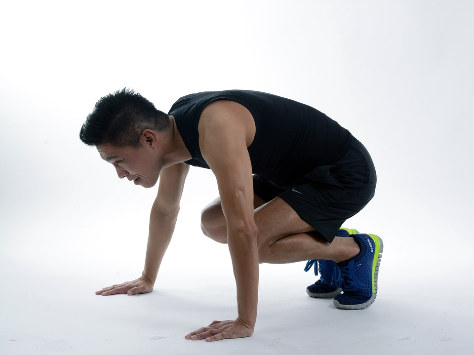 A man doing one of the burpees position ready to jump.