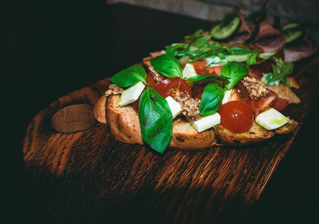 close up of a sandwich with fresh basil, tomatoes, and mozzarella cheese