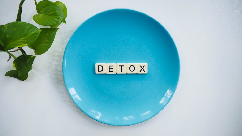"""Tiled text read as """"detox"""" for body cleanse on a teal colored ceramic plate next to a branch of leaves."""