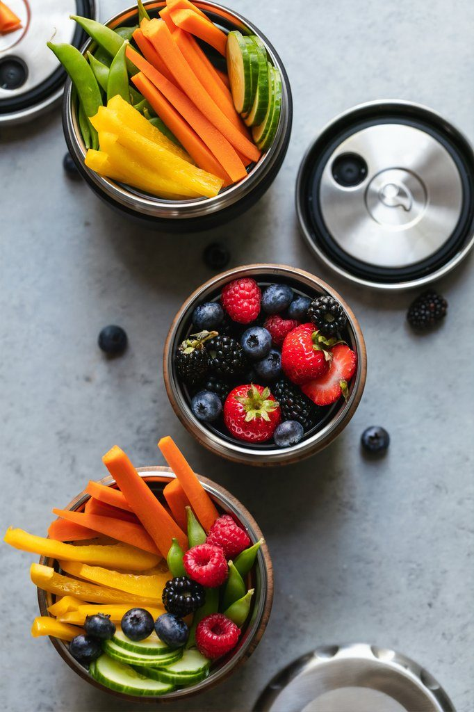Three bowls of vegetables and berries.