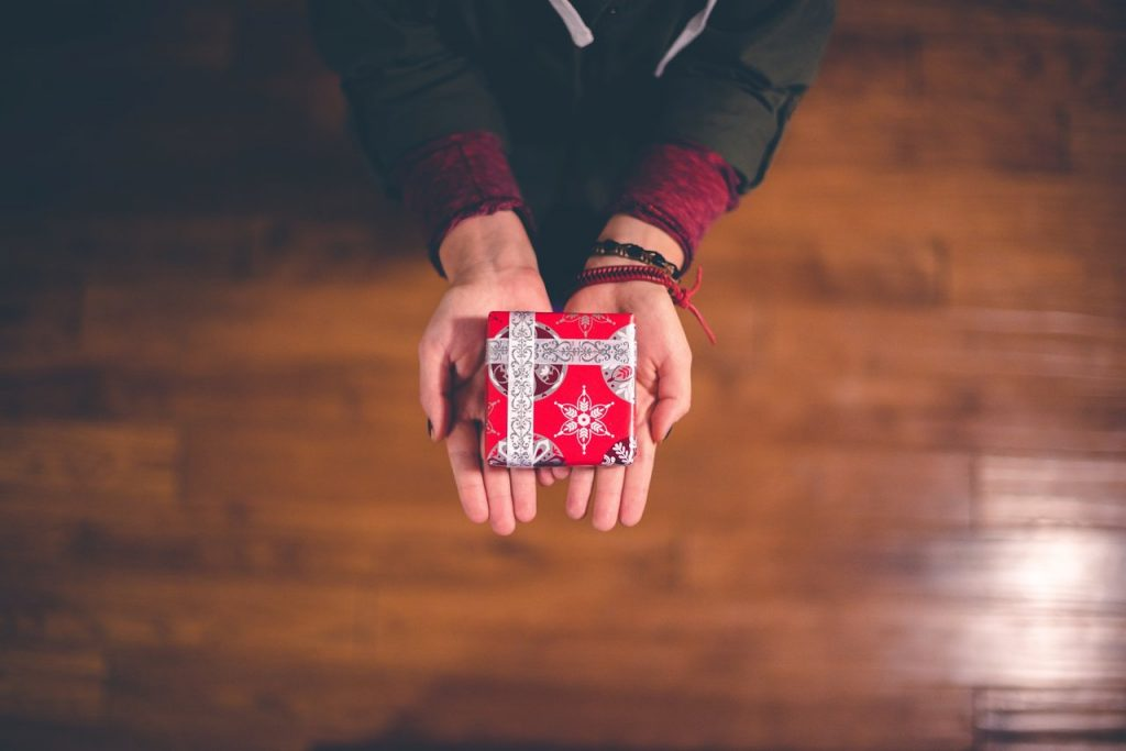 Person holding out a gift for the holidays. Do you have some ideas for holiday gifts?