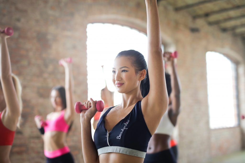 Woman lifting weights in exercise class, doing some morning workouts.